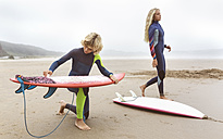Spain, Aviles, two young surfers on the beach preparing their surfboards - MGOF03549
