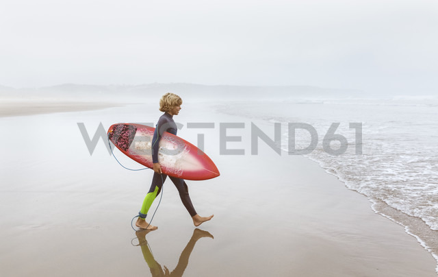 Spain, Aviles, young surfer walking towards the water - MGOF03555 - Marco Govel/Westend61