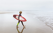 Spain, Aviles, young surfer walking towards the water - MGOF03555