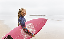 Spain, Aviles, young surfer holding surfboard on the beach - MGOF03561