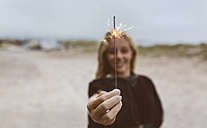 Spain, Aviles, teenage girl holding a sparkler on the beach - MGOF03567