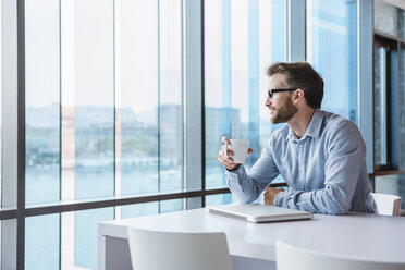 Man with laptop and coffee cup sitting in modern office building - DIGF02727