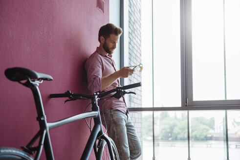 Man with bicycle standing in modern office looking at cell phone - DIGF02742