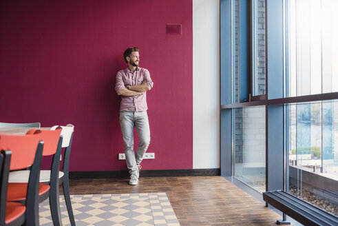 Man leaning against purple wall in modern office looking out of window - DIGF02745