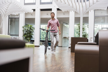 Man with bicycle walking in office - DIGF02748