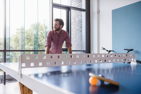 Man in break room of modern office at table tennis table - DIGF02751