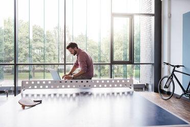 Man using laptop in break room of modern office on table tennis table - DIGF02754