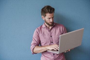 Man using laptop against blue wall - DIGF02757