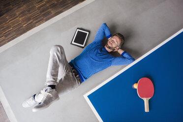 Man lying on the floor with tablet in break room of modern office - DIGF02763