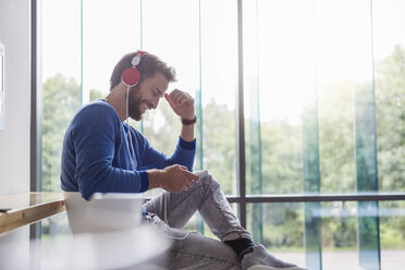 Happy man with cell phone listening to music with headphones - DIGF02769