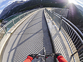 Italy, Lombardy, Sondrio, biker on dam wall of Cancano dam - LAF01877