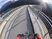 Italy, Lombardy, Sondrio, biker on dam wall of Cancano dam - LAF01877