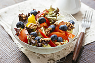 Glass bowl of mixed salad with different raw vegetables, blueberries and walnuts - HAWF00962