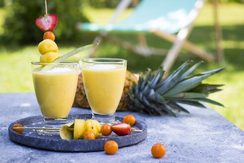 Two glasses of tropical smoothie with pineapple, mango, coconut milk and coconut flakes - YFF00672