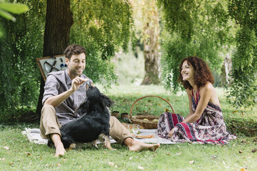 Couple with dog having a picnic in a park - ALBF00152