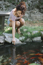 Woman crouching at a pond in a park - ALBF00155