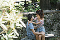 Couple in love hugging on bench in a park - ALBF00158