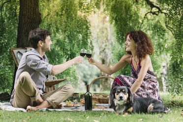 Couple with dog having a picnic in a park drinking red wine - ALBF00161