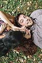Happy couple in love with dog lying on a meadow - ALBF00170