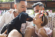 Gay couple with daughter and dog on balcony - MRAF00224