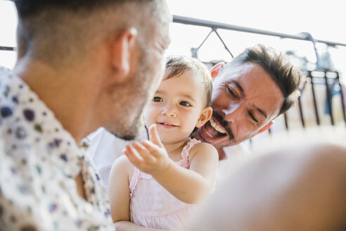 Happy gay couple with daughter on balcony - MRAF00248