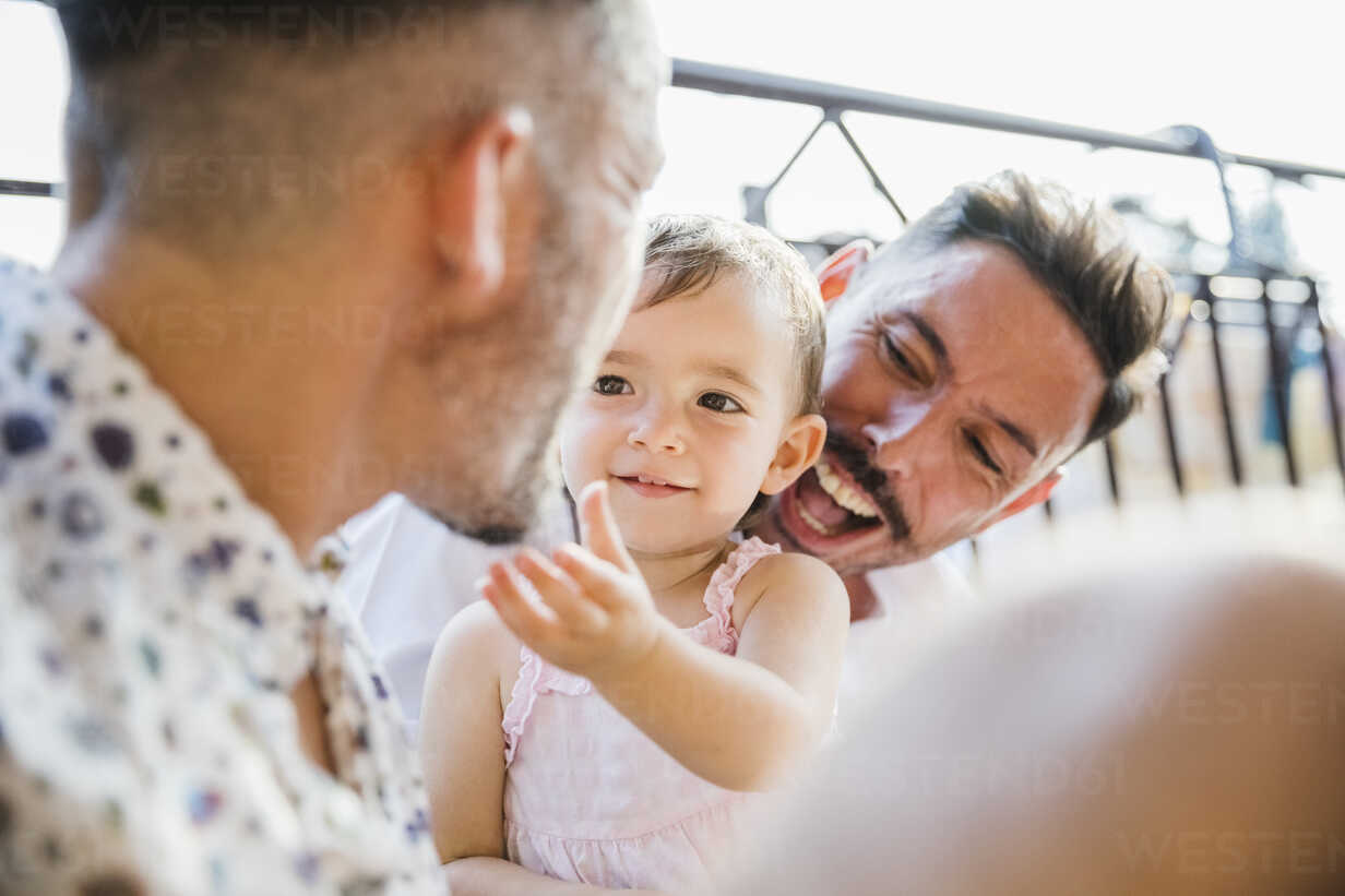 Happy gay couple with daughter on balcony - MRAF00248 - Michela Ravasio/Westend61