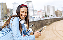 Spain, Gijon, smiling young woman with cell phone and headphones at waterfront promenade - MGOF03572