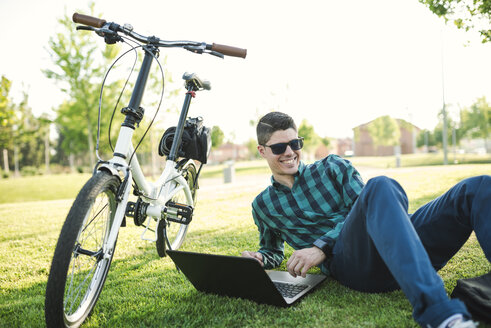 Young man with bicycle using laptop in a park - RAEF01906