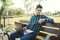 Young man with laptop on park bench checking the time - RAEF01909