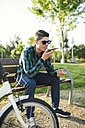 Young man sending a voice mail in a park - RAEF01912
