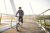 Young man riding bicycle on a bridge at sunset - RAEF01918