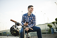 Happy young man with bicycle and cell phone - RAEF01927
