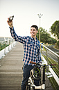 Smiling young man with folding bicycle on a bridge taking a selfie - RAEF01930