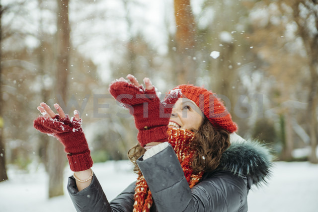 Happy woman catching snowflakes - ZEDF00804