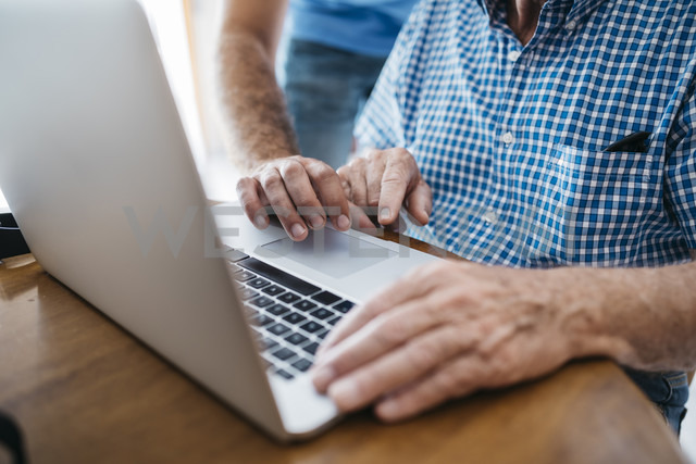 Adult grandson teaching his grandfather to use laptop, close-up - JRFF01413