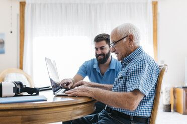 Adult grandson teaching his grandfather to use laptop - JRFF01419