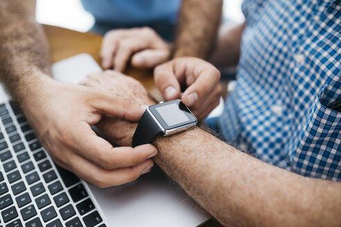 Adult grandson teaching his grandfather to use smartwatch, close-up - JRFF01422
