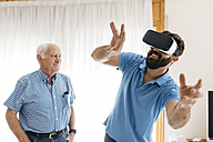 Smiling man using Virtual Reality Glasses at home while his grandfather watching him - JRFF01425