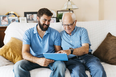 Adult grandson teaching his grandfather to use tablet - JRFF01428