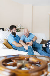 Adult grandson and his grandfather sitting on the couch at home tickling each other - JRFF01431