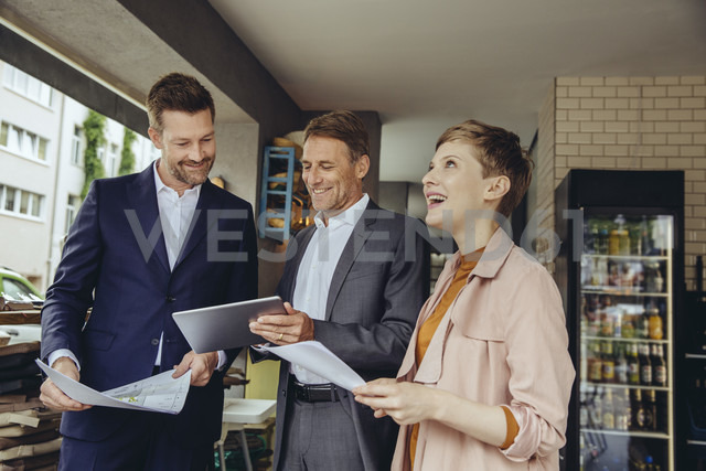 Woman and two businessmen discussing plans in a cafe - MFF03818