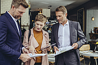 Woman and two businessmen discussing plans in a cafe - MFF03821