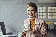 Portrait of smiling woman in cafe with laptop and cup of coffee - MFF03827
