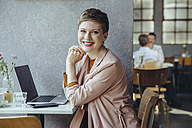 Portrait of smiling woman in cafe with laptop - MFF03830