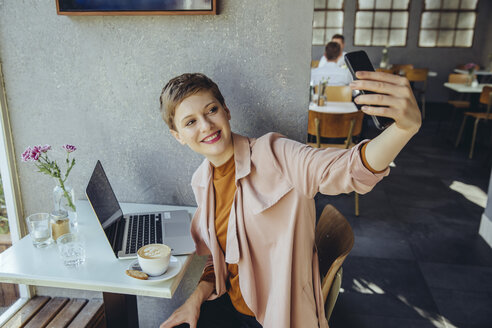 Woman taking a selfie with coffee and laptop in cafe - MFF03833
