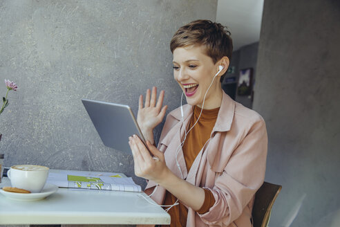 Woman with tablet waving to somebody during a video conference in a cafe - MFF03836