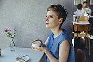 Serious woman with a cup of coffee in a cafe - MFF03842