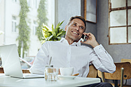 Smiling businessman on the phone in cafe - MFF03857