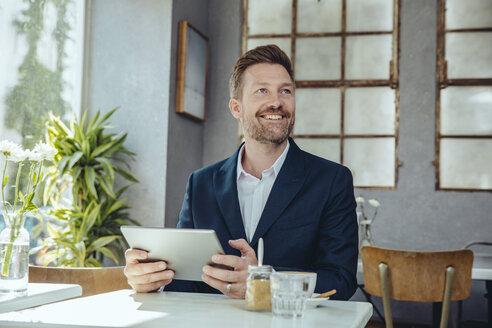 Smiling businessman with tablet in a cafe looking up - MFF03860