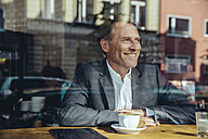 Smiling businessman in cafe looking out of window - MFF03866